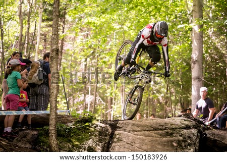 MONT STE-ANNE, QUEBEC, CANADA - AUGUST 11: Downhill Men Junior, CAN - VEZINA McKay about to crash, UCI World Cup on Aug. 11, 2013 - stock photo