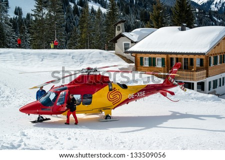 MONTAFON, AUSTRIA - MARCH 16, 2013: A rescue helicopter ready to evacuate a skier after a heavy accident in Montafon, Austria. Skiing safety is becoming more and more of an issue due to crowded slopes - stock photo