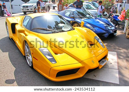 MONTE CARLO, MONACO - AUGUST 2, 2014: Yellow and blue supercars Enzo Ferrari at the city street. - stock photo