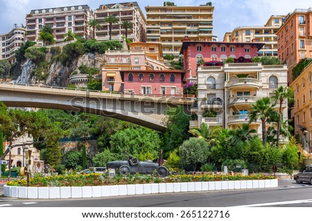 MONTE CARLO, MONACO - JULY 13, 2013: Colorful buildings and sculpture of William Grover-Williams in Bugatti racing car- the first winner of Monaco Grand Prix on April 14, 1929. - stock photo