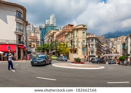 MONTE CARLO, MONACO - JULY 13, 2013: Policewoman from Urban Police Division stand on roadway near roundabout and controls traffic. National police force of Monaco consisting of 515 police officers. - stock photo