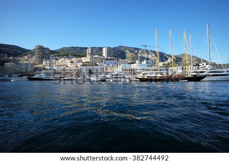 MONTE CARLO, MONACO - September 20, 2015: View from sea on different boats in port of Monte Carlo on urban coastline with mountains background, horizontal photo