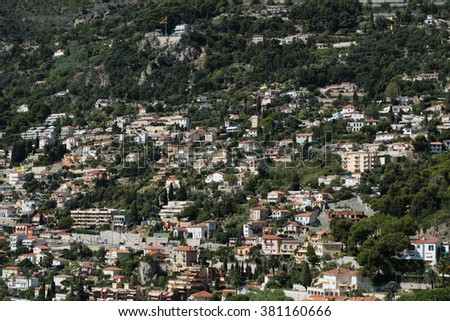 Monte Carlo, Monaco - September 20, 2015: view of mountain with densely populated city with residential buildings green trees on cityscape background, horizontal picture