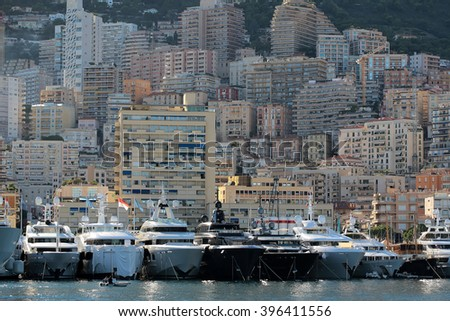 Monte Carlo, Monaco - September 20, 2015: yachts and sailboats modern vessels at moorage in sea port on sunny summer day against mountains on cityscape background, horizontal picture