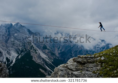 "MONTE PIANA, DOLOMITES/ITALY - SEPTEMBER 08, 2013: an acrobat on a rope tended above an abyss during ""Highline Meeting"" of tightrope walkers from around the world taking place every year on september"