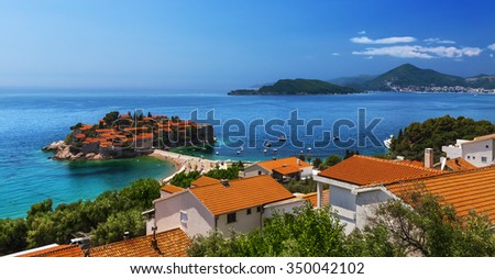 Montenegro. General view of Sveti Stefan village with the island connected to land by a narrow isthmus and the coastal area around Budva town in the background - stock photo
