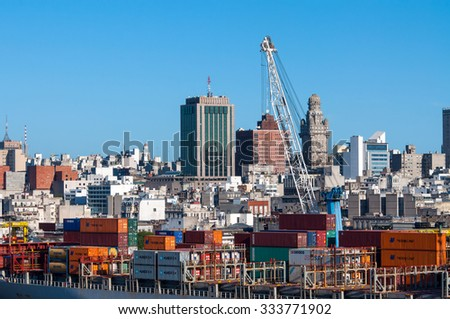 MONTEVIDEO, URUGUAY - DECEMBER 15, 2012: Montevideo cityscape from port district - Containers at the port, on the ship in the foreground at Montevideo, Uruguay.