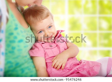 Monther with a smiling little girl over green window - stock photo