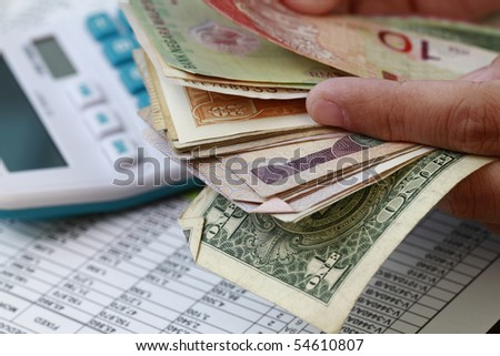 Monthly report, calculator and counting the money - stock photo