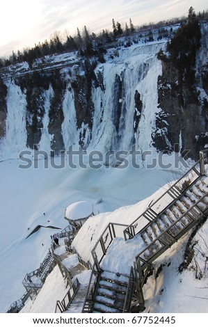 Montmorency Falls in winter The Montmorency Falls, or Chutes Montmorency in French, is located 7 km east of Quebec City. The falls is frozen in winter. - stock photo