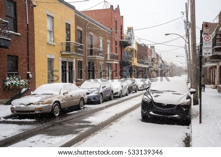 Montreal, CA - 5 December 2016: Street in Le Plateau with cars covered in snow