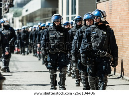 MONTREAL, CANADA   APRIL 02 2015: Riot in the Montreal Streets to counter the Economic Austerity Measures. Cops Following Marchers in case of something Goes Wrong - stock photo