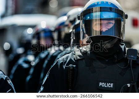 MONTREAL, CANADA   APRIL 02 2015: Riot in the Montreal Streets to counter the Economic Austerity Measures. Closeup of Cops Portraits Ready in case of Problem - stock photo