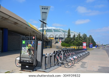 MONTREAL CANADA AUGUST 08 2015. Bixi stand in front the Montreal Olympic Stadium and tower. It's the tallest inclined tower in the world.Tour Olympique stands 175 meters tall and at a 45-degree angle  - stock photo