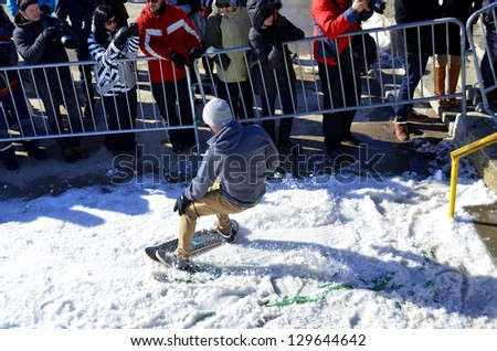 MONTREAL CANADA FEBRUARY 17: Unidentified participant in snowboarding at the Barbegazi Winter Extreme Sports Festival in front the Olympic Stadium on February 17 2013 in Montreal Canada - stock photo
