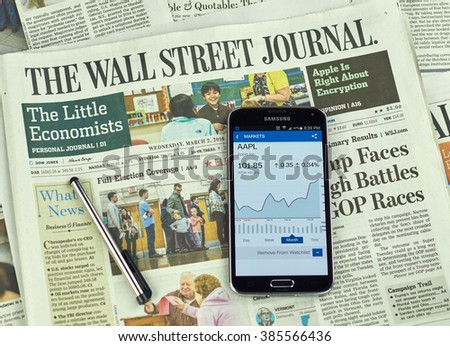 MONTREAL, CANADA - MARCH 3, 2016 - The Wall Street Journal Newspaper with Samsung S5 on it. The Wall Street Journal Is an American international daily newspaper. - stock photo