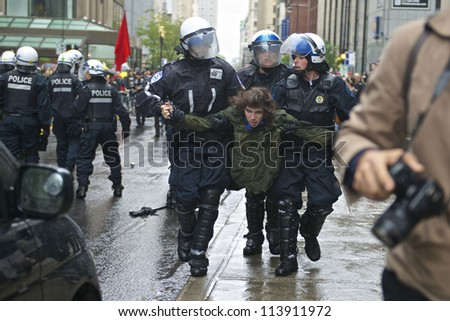 MONTREAL, CANADA - SEPTEMBER 22: Police in riot gear carry an unidentified protester after he damaged a police vehicle from a student rally demanding free tuition on September 22, 2012 in Montreal. - stock photo