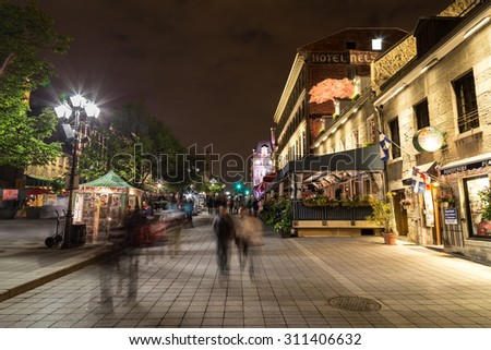 MONTREAL, CANADA - 17TH MAY 2015: A view of buildings in Old Town Montreal at night showing the blur of people. - stock photo