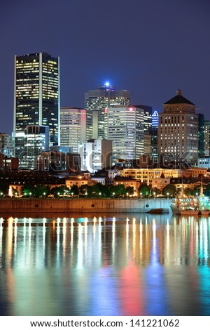 Montreal over river at dusk with city lights and urban buildings - stock photo