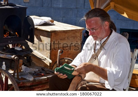 MONTREAL QUEBEC CANADA AUGUST 24: Man as spoons maker re-enacting New France period in Old Montreal, Pointe-a-Calliere's 18th Century Public Market on august 24 2013 in Montreal Canada - stock photo