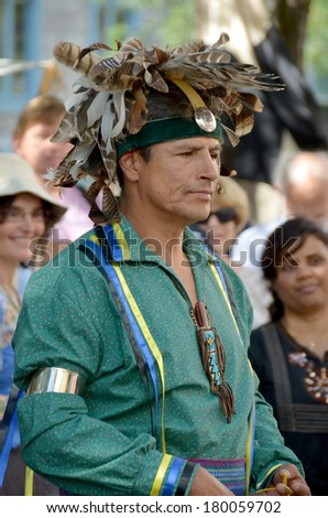 MONTREAL QUEBEC CANADA AUGUST 24: Man wears as indian re-enacting New France period in Old Montreal, Pointe-a-Calliere's 18th Century Public Market on august 24 2013 in Montreal Canada - stock photo