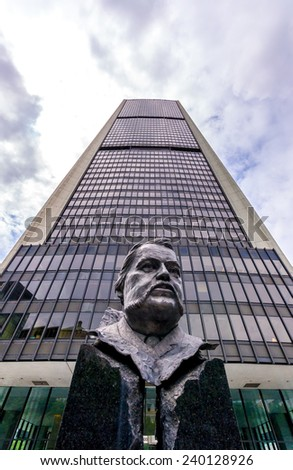 Montreal,Quebec,Canada- July 26-2012: Bust of Joseph Xavier Perrault 1838-1905, Founder of the Chamber of Commerce of Montreal and in the background The Exchange Tower in Montreal.  - stock photo