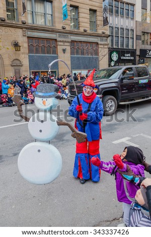 MONTREAL, QUEBEC, CANADA - NOVEMBER 21, 2015 : Little viewer girl takes part in the 65th edition of the Santa Claus Parade Destination Centre-ville (Defile du Pere Noel) along Saint Catherine Street. - stock photo