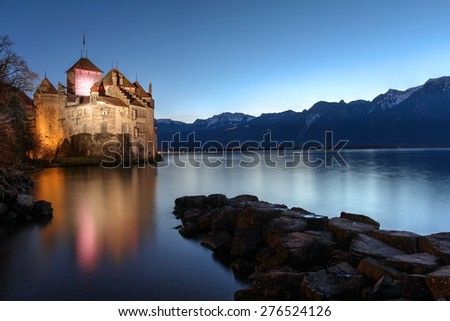 MONTREUX, SWITZERLAND - JANUARY 4: Chateau de Chillon, Switzerland at sunset time reflecting in the waters of Lake Geneva (Leman) near Montreux, on the evening of Jan 4, 2015. - stock photo