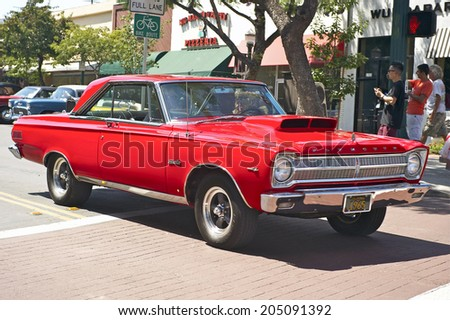 MONTROSE/CALIFORNIA - JULY 6, 2014: 1965 Plymouth Satellite owned by Greg and Christy Davie as it departs the Montrose Hot Rod & Classic Car Show. July 6, 2014 Montrose, California USA  - stock photo