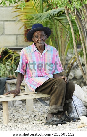 MONTROUIS, HAITI - DECEMBER 2, 2014:  An elderly Haitian man sitting on a bench under small palm trees.