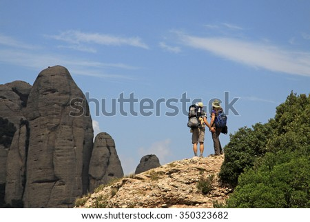 MONTSERRAT, SPAIN - AUGUST 28, 2012: Tourists on hiking path in the mountains near Benedictine abbey Santa Maria de Montserrat in Monistrol de Montserrat, Spain