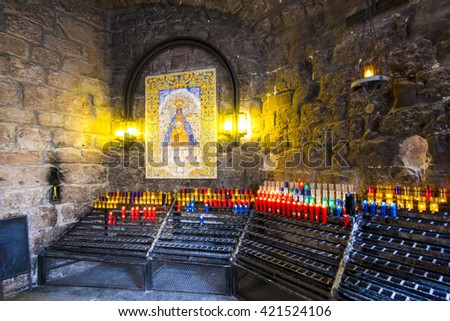 MONTSERRAT, SPAIN-MAY 22, 2009: Candles in the Benedictine abbey Santa Maria de Montserrat in Monistrol de Montserrat, Spain - stock photo