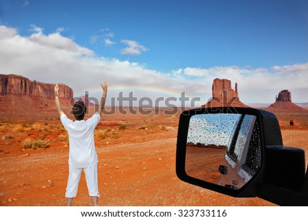 Monument Valley. Arizona, USA. The unique red sandstone buttes are reflected in the car mirror. The woman -  tourist threw up her hands in delight - stock photo