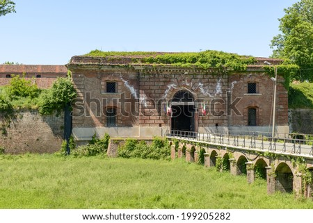 monumental entrance of Cittadella fortifications, Alessandria, Italy. view of entrance door in the brick walls on the green dry moat of ancient fortified part of the city, shot in bright summer light  - stock photo