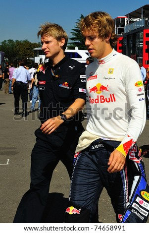 MONZA - SEPTEMBER 11: Sebastian Vettel is walking whit a team member to his car in the pitbox on september 11, 2010 in monza, italy, formula 1 - stock photo