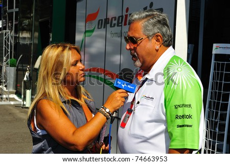 MONZA - SEPTEMBER 11: Vijay mallya of the Force India F1 team is talking to a lady of the press in the paddock on september 11, 2010 in monza, italy - stock photo