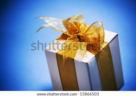 mood shot of luxurious gift box on blue background - intentional selective focus & vignetting - stock photo