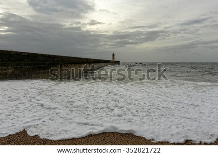 Moody autumn seascape with tide foam in the foreground. Senhora da Luz beach, near the Douro river mouth, Porto, Portugal - stock photo