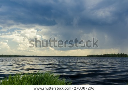 Moody dramatic cloudscape with dark summer forest lake before stormy rain - stock photo