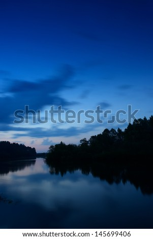 Moody Lake after Sunset, some mist on the water - stock photo