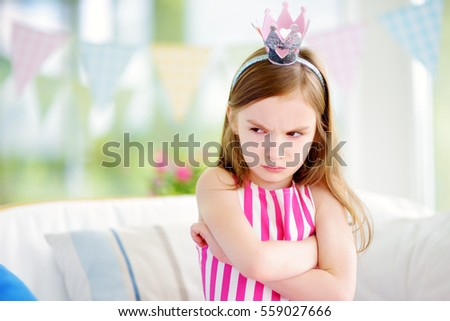 Moody little girl wearing princess tiara feeling angry and unsatisfied. Children tantrum concept.