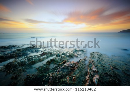 Moody seascape with foreground rocks at sunset