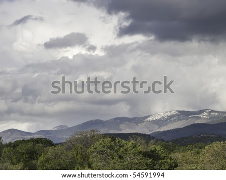 Moody sky over outskirts of Santa Fe in May, with snow on mountaintops