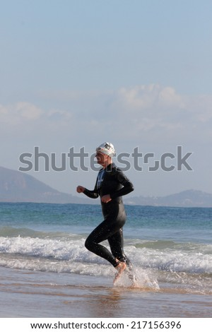 "MOOLOOLABA, AUSTRALIA - SEPTEMBER 14 : Unidentified competitor in the ""Ironman 70.3"" triathlon on September 14, 2014 in Mooloolaba, Australia"