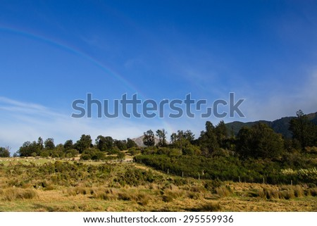 Moon and rainbow in the sky above moutain pasture, Canterbury, New Zealand - stock photo
