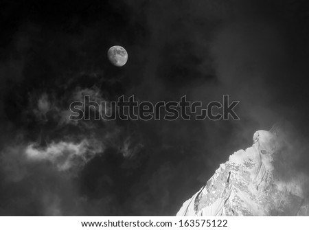 Moon and slope of the Nuptse (7864 m) at sunset (view from Kala Patthar) - Everest region, Nepal, Himakayas (black and white) - stock photo