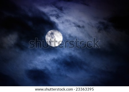 Moon at midnight with clouds covering the moon slightly - stock photo