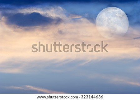 Moon clouds is a soft colorful scenic cloudscape against a blue sky with the full moon rising in a blue sky as it sits behind some wispy clouds. - stock photo