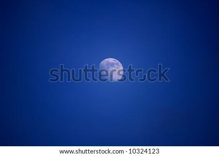 Moon isolated on the blue sky - stock photo