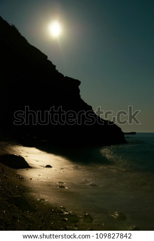 Moon night on the sea with waves and rocks. - stock photo